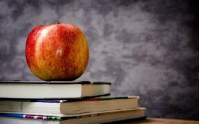 mela rossa su pila di libri