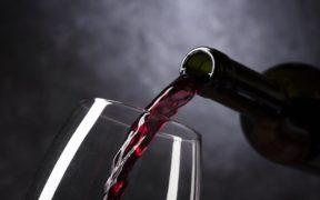 vino rosso versato in un bicchiere in vetro