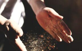 mani che alzano farina bianca controluce