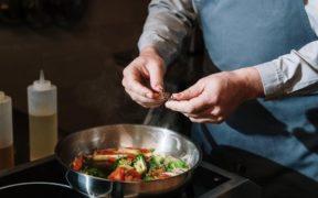 cuoco che mette origano in una padella con verdure